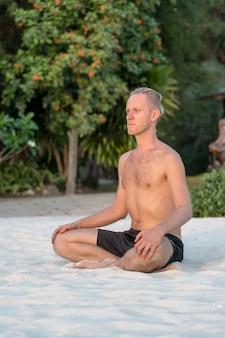 Jonge kerel met dreadlocks doet yoga op een tropisch strand, close-up. het concept van een gezonde levensstijl