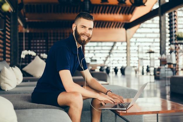 Jonge kerel met een baard werkt in een café, freelancer maakt gebruik van een laptop, doet een project