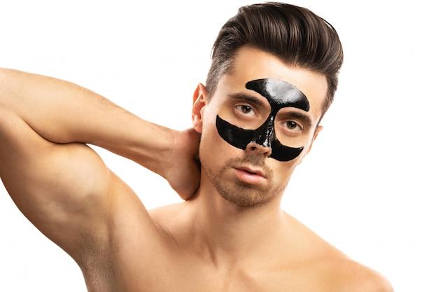 Jonge kerel met een zwart houtskoolmasker op zijn gezicht op wit.