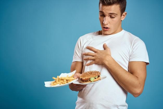 Jonge kerel met frietjes en hamburger op blauwe achtergrond geïnteresseerd blik emoties fastfood calorieën bijgesneden weergave kopie ruimte