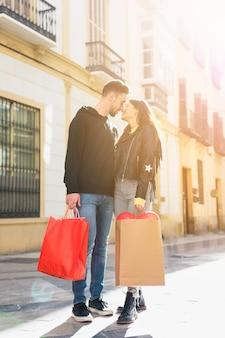 Jonge kerel met pakketten die dame op straat kussen