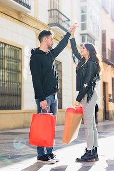Jonge kerel met pakketten die upping hand van gelukkige dame op straat houden