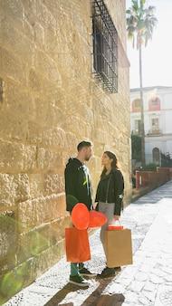 Jonge kerel met pakketten en ballons dichtbij dame op straat