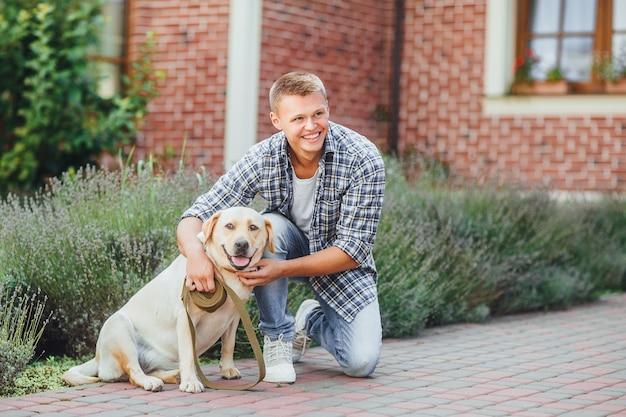 Jonge kerel met retriever op wandeling in zomerpark. knappe man met zijn hond golden retriever buitenshuis.