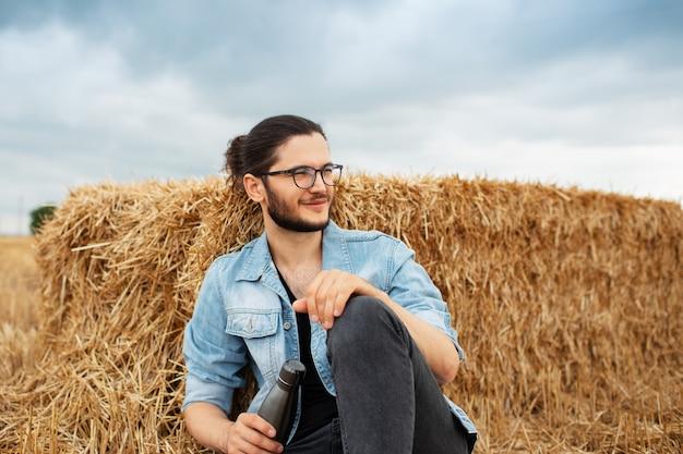 Jonge kerel met stalen thermofles, zittend in het veld in de buurt van hooibergen.