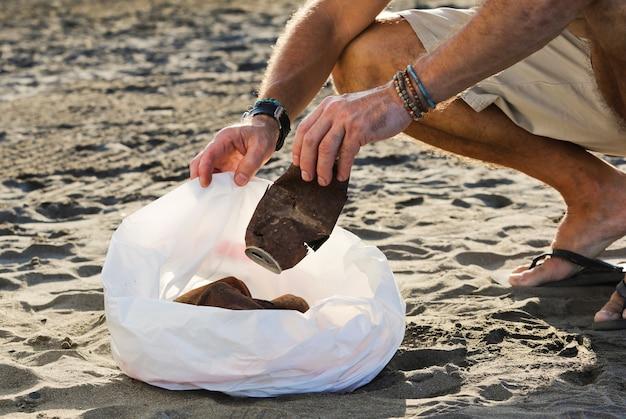 Jonge kerel met vuilniszak en roestige blikjes binnenshuis op het strand