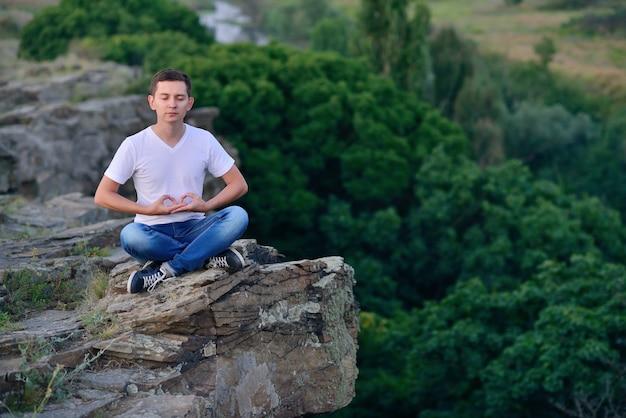 Jonge kerel op de rand van een klif mediteren