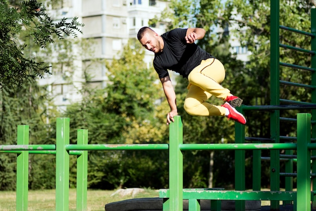 Jonge kerel springen en straat training en parkour buiten in park doen