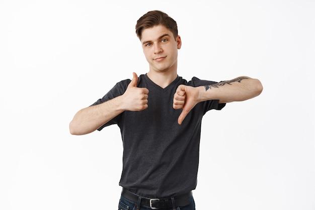 Jonge kerel, student toont duimen omhoog duim omlaag, gemiddelde snelheid, besluit nemen, leuk vinden of niet leuk vinden, staande op wit