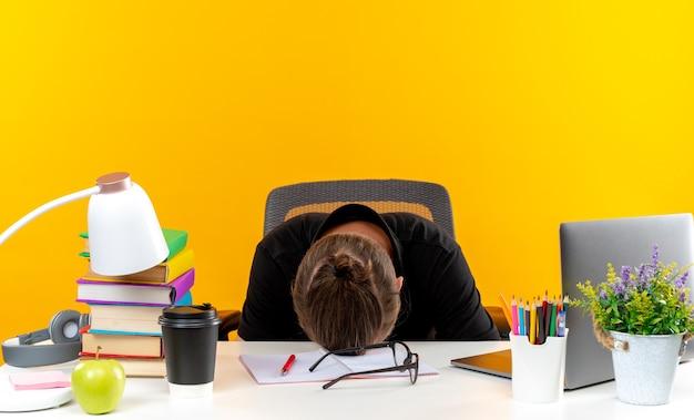 Jonge kerel student zittend aan tafel met schoolhulpmiddelen neergelaten hoofd op tafel geïsoleerd op oranje muur