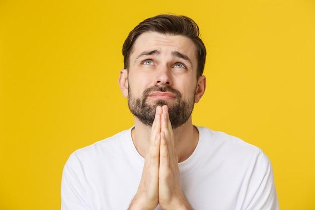 Jonge kerel terloops gekleed geïsoleerd op gele ruimte, handen in elkaar gezet in gebed of meditatie, er ontspannen en kalm uitzien Premium Foto
