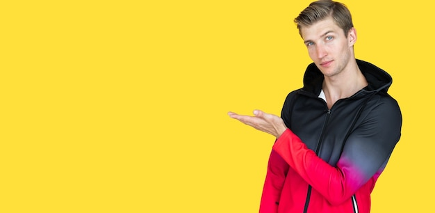 Jonge kerel van europees uiterlijk op een gele achtergrond. houdt één handpalm open. ruimte kopiëren