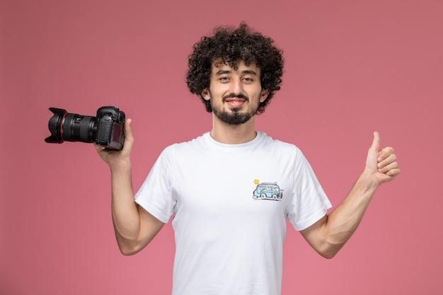 Jonge kerel verschijnt duimen en houdt zijn fotocamera