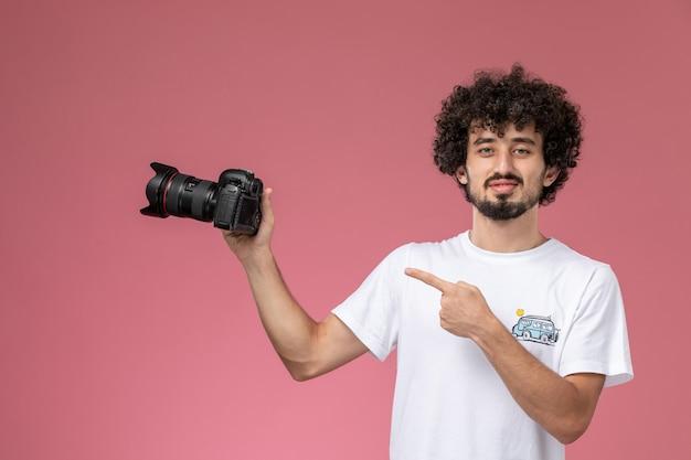 Jonge kerel wijst op zijn nieuwe fotocamera