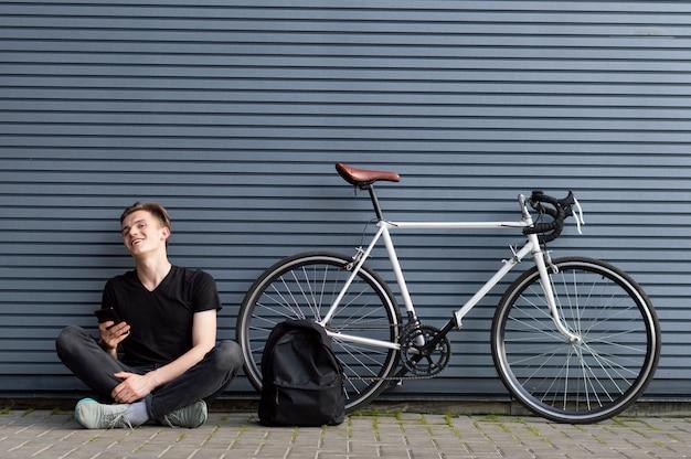 Jonge kerel zitten met een rugzak en een smartphone in de buurt van de fiets