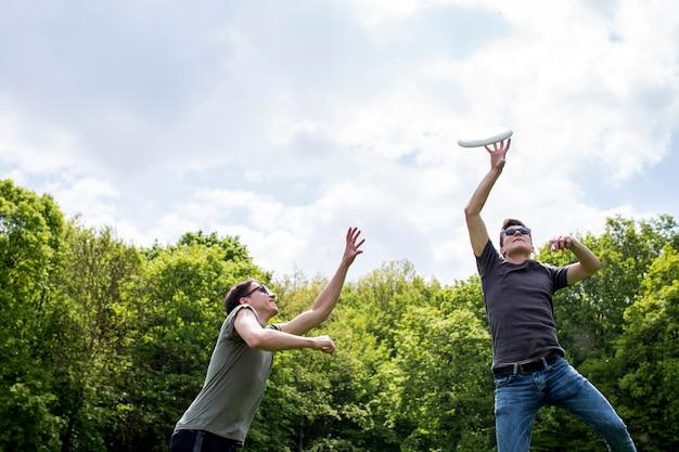 Jonge kerels die frisbee in aard spelen