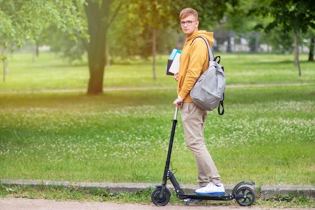 Jonge kerelstudent met boeken en rugzak die op elektrische autoped in park berijden