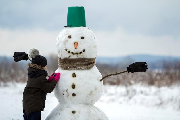 Jonge kind jongen klaar met lachende sneeuwpop in emmer hoed, sjaal en handschoenen op lege winter veld landschap en helderblauwe hemel kopie ruimte.