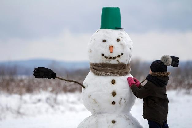 Jonge kind jongen klaar met lachende sneeuwpop in emmer hoed, sjaal en handschoenen op lege winter veld landschap en heldere blauwe hemel kopie ruimte achtergrond. vrolijk kerstfeest, gelukkig nieuwjaar wenskaart.