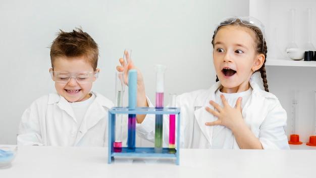 Jonge kind wetenschappers plezier doen experimenten in het laboratorium