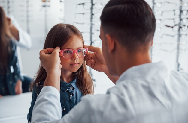 Jonge kinderarts in witte jas helpt bij het krijgen van een nieuwe bril voor een klein meisje.