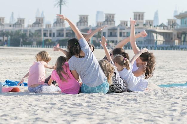 Jonge kinderen doen oefeningen buiten op het strand met wit zand naast de zee