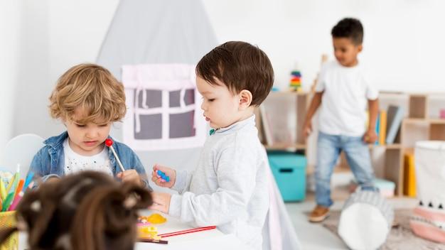 Jonge kinderen spelen samen thuis