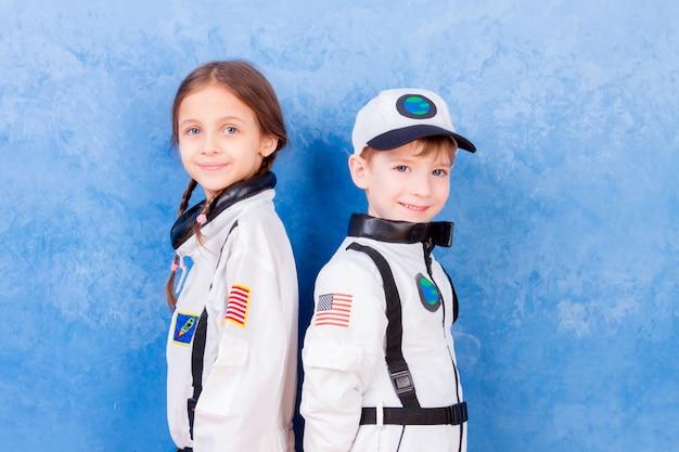 Jonge kinderenjongen en meisje die in astronaut in wit astronautenkostuum spelen en over het vliegen in kosmos dromen
