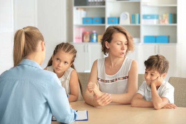 Jonge kinderpsycholoog die met familie in bureau werkt