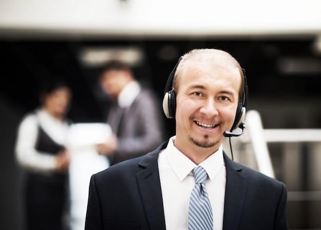 Jonge klantenservicemedewerker die op de hoofdtelefoon spreekt