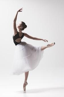 Jonge klassieke danser die op wit danst. ballerina-project.