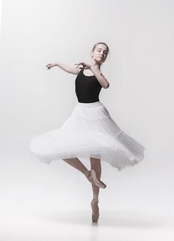 Jonge klassieke danser die op wit danst