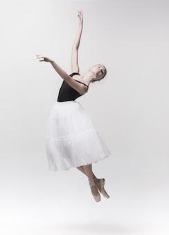 Jonge klassieke danser die op witte achtergrond wordt geïsoleerd.