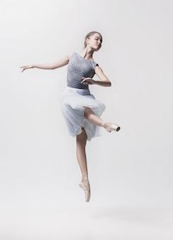 Jonge klassieke danser die op witte ruimte wordt geïsoleerd.