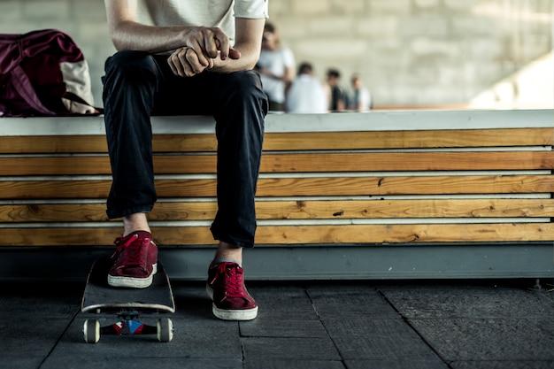 Jonge klassieke skateboard rijder dicht koelen in de straat levensstijl.