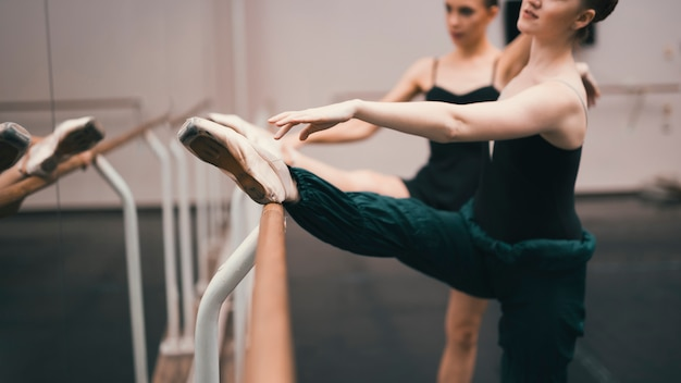 Jonge klassieke vrouwelijke dansers die in de dansstudio praktizeren