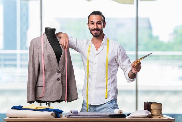 Jonge kleermaker die aan nieuw kledingontwerp werkt