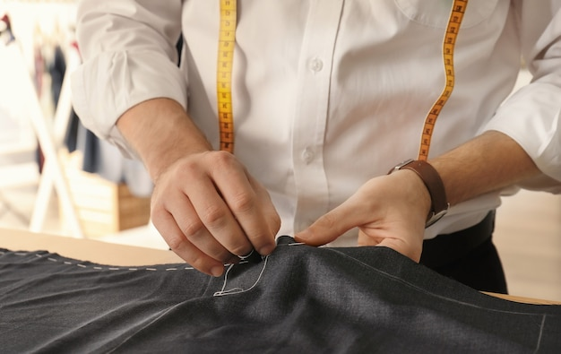 Jonge kleermaker die in atelier werkt