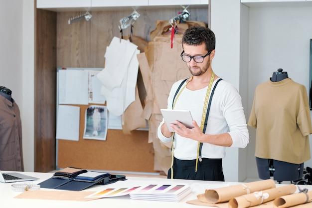 Jonge kleermaker in vrijetijdskleding tabletscherm kijken tijdens het surfen door websites met modetrends in zijn atelier