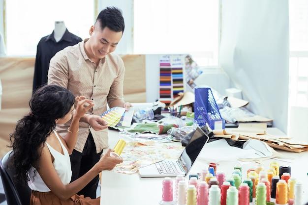 Jonge kleermakers die een palet van monsters gebruiken bij het kiezen van de perfecte tint gele draad voor stof