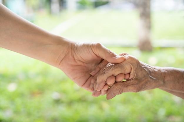 Jonge kleindochter die met tederheid en zorg voor grootmoeder zorgt