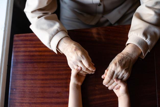 Jonge kleindochter die teder en zorgzaam voor oma zorgt. gerimpelde handen van een zeer oude vrouw en jonge handen van een tienervrouw van dichtbij, de verandering van de familiegeneratie. zorg en welzijn.