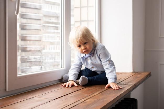 Jonge kleine kind peuter jongen zittend op het raam en glimlachen