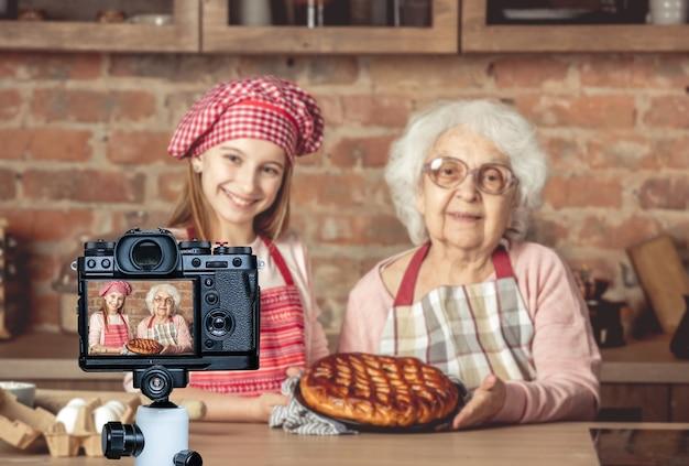Jonge kleine kleindochter met haar oma die een dienblad vasthoudt en zelfgemaakte fruittaart laat zien die ze samen hebben gebakken