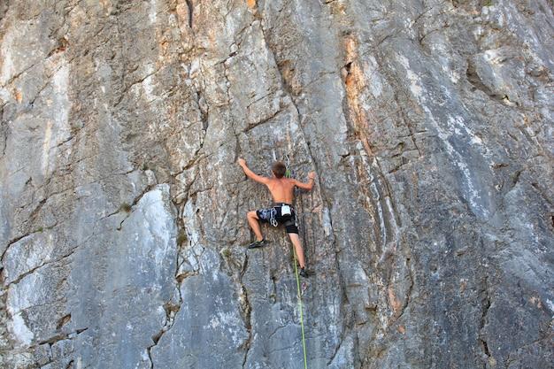 Jonge klimmer die op sistiana-rots, triëst beklimt