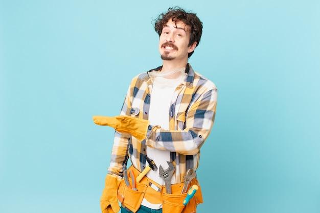 Jonge klusjesman huishoudster lacht vrolijk, voelt zich gelukkig en toont een concept