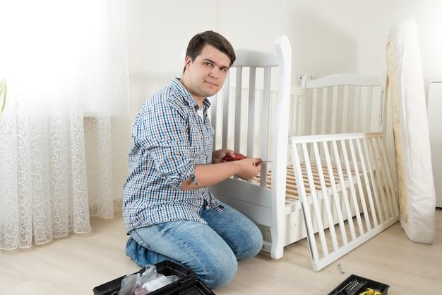 Jonge klusjesman zittend op de vloer in een lege kamer en nieuwe meubels in elkaar zetten