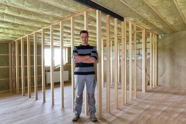 Jonge knappe aannemersmens die zich in het midden van grote ruime lichte lege zolderruimte bevinden met eiken vloer