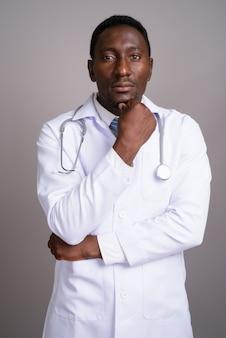 Jonge knappe afrikaanse man arts tegen een grijze achtergrond