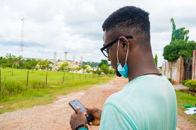 Jonge knappe afrikaanse man die buiten zit met een gezichtsmasker om te voorkomen, voorkomen, te voorkomen dat hij de uitbraak in de samenleving uitbreekt terwijl hij zijn mobiele telefoon bedient